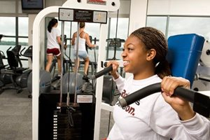 Student working out on weight equipment