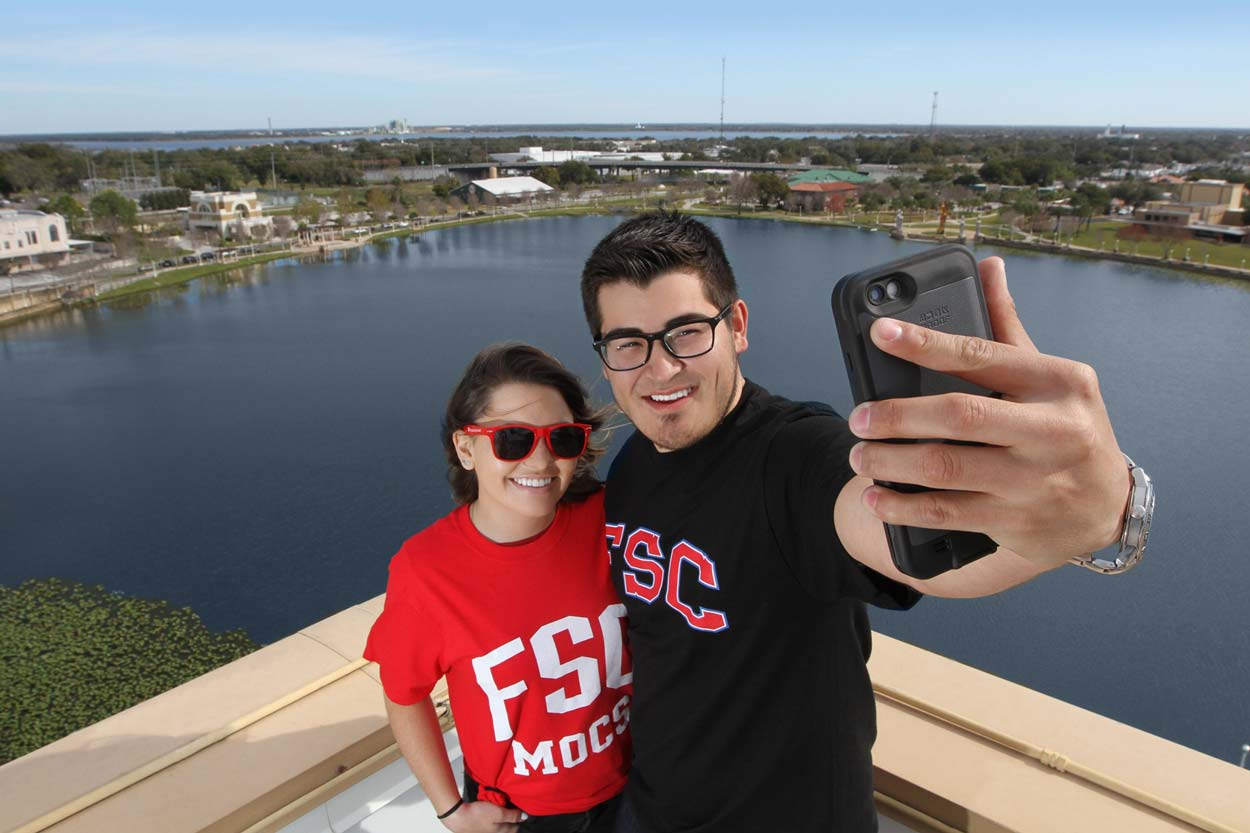 students take a selfie overlooking the beautiful lake mirror area in downtown lakeland, florida