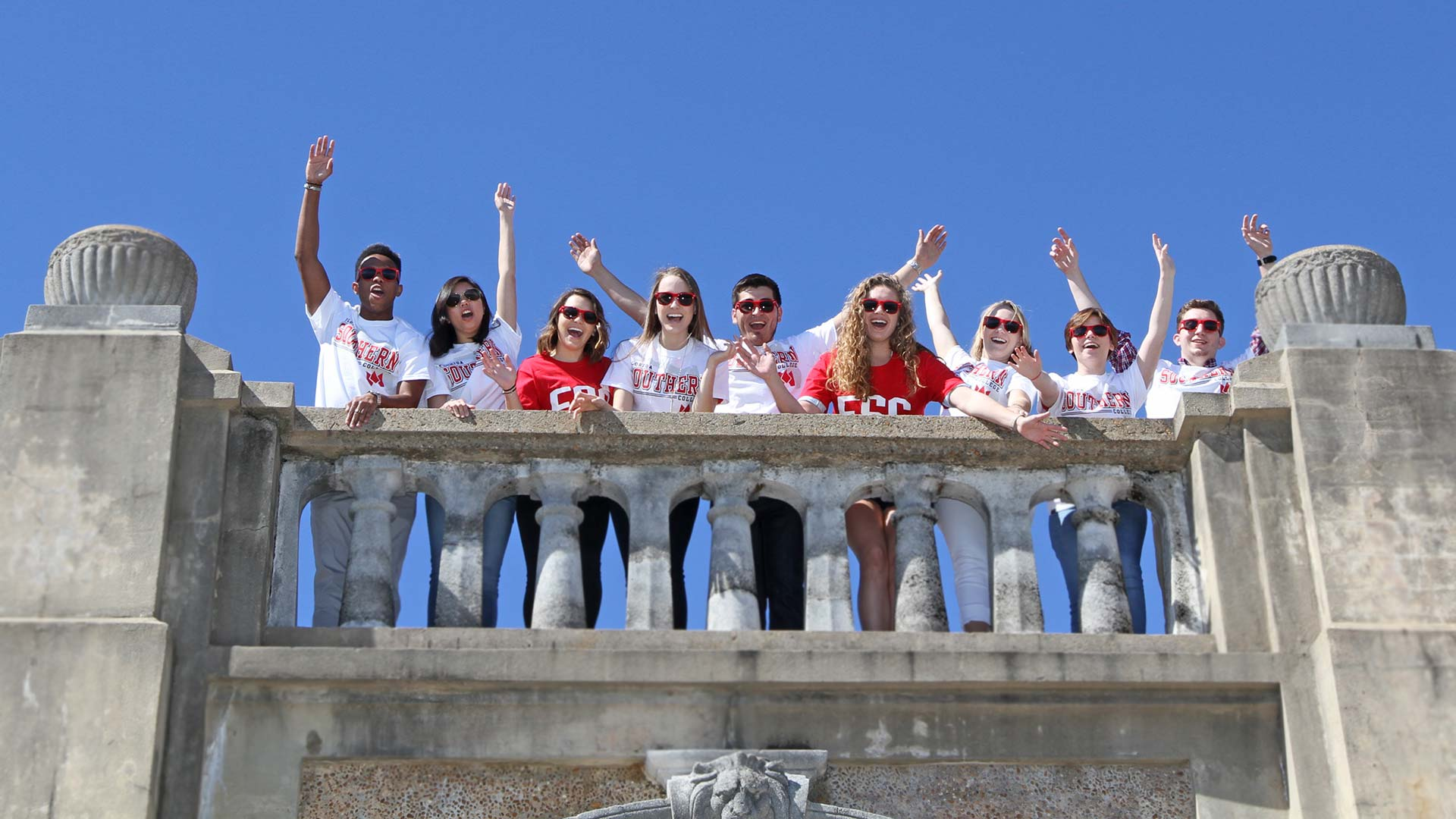 Students cheering from atop of bridge