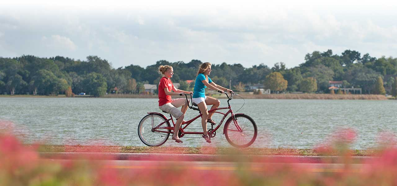 students riding a bike around lake hollingsworth