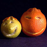 citrus fruits with smiley faces cut into them