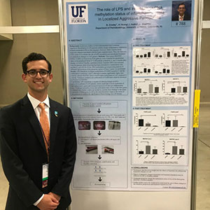 Blake Crosby stands next to the poster summarizing his award-winning research at UF.