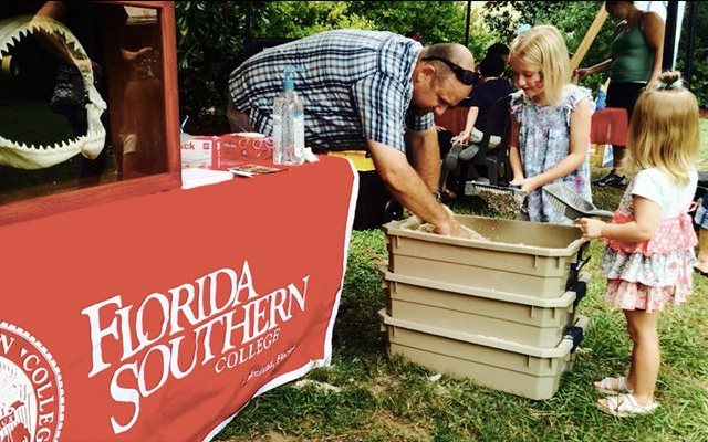 Dr. Bryan Franks helps two children find fossil shark teeth at the North Florida Shark Festival at the Jacksonville Zoo.