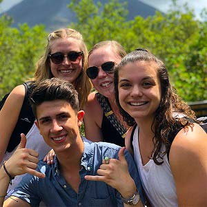 Jessie '20 (front right) at the top of a mountain overlooking the beautiful Volcano with three other students.