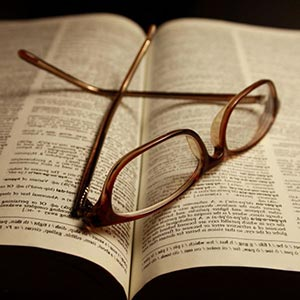 Glasses laying  on a book.