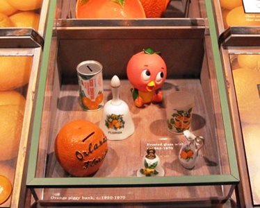 Orange County Regional History Center display with Orange Bird figurine, orange-themed coin bank, bell, and cup